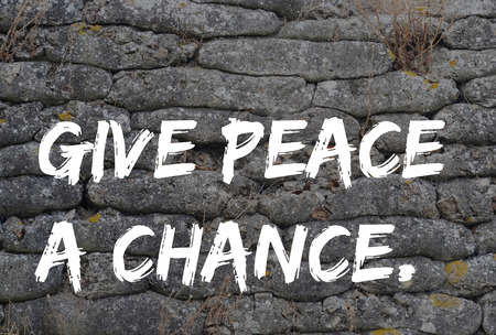 fossilized: Give peace a chance, text in graffiti style on trench from World War I, relic, fossilized sandbags, background