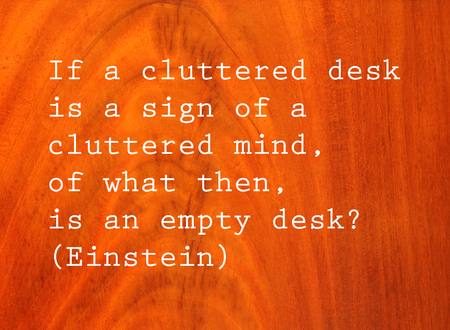 cluttered: If a cluttered desk is a sign of a cluttered mind, of what then is an empty desk? Text by Albert Einstein on antique cherry wood  background Stock Photo