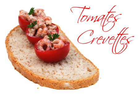 french text: Three cocktail tomatoes with shrimps and parsley on a slice of bread, on white, with easy removable French text Tomates Crevettes meaning tomatoes with shrimps, shallow dof