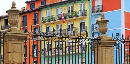 colourful houses behind fence with the basque flag hanging out in pamplona, basque country, spain, europe