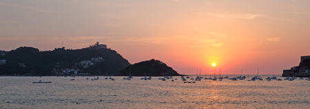 sunset over the sea with view over the island Santa Klara in San Sebastian, Basque Country, Span, Europe Stock Photo