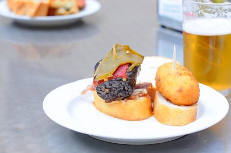 Basque tapas or pintxos with beer in San Sebastian, selective focus Stock Photo