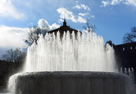 fountain at the south side of castello sforzesco in Milan with blue sky and white fluffy clouds in the background, backlit