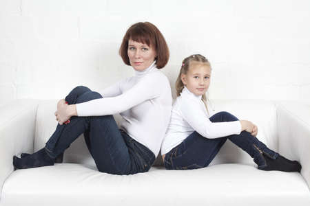 mother with the daughter sit on a sofa in identical clothes