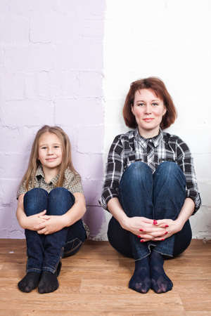 mother with the daughter in jeans and a shirt sit on a floor against a wall from two flowers Stock Photo