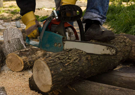 chainsaw on the background of sawn logs. firewood for the winter