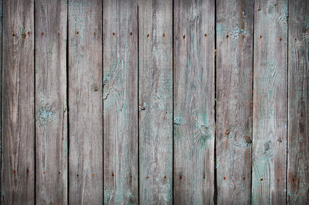 Wooden Palisade background. Close up of grey and green wooden fence panels.
