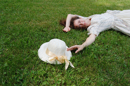 admire: European woman laying on grass and touching her hat in vintage dress in park.
