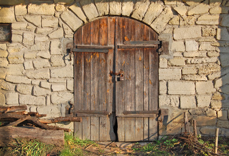 Gray old surface with doors at the sunlight. Ancient stable Zdjęcie Seryjne