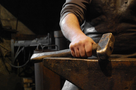 forge: Blacksmith sitting in forge and holding hammer in hand on the anvil