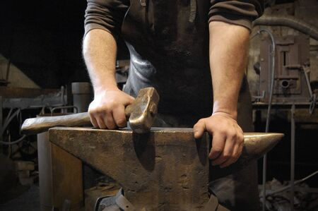 forge: Blacksmith standing and holding hammer in hand on the anvil in forge