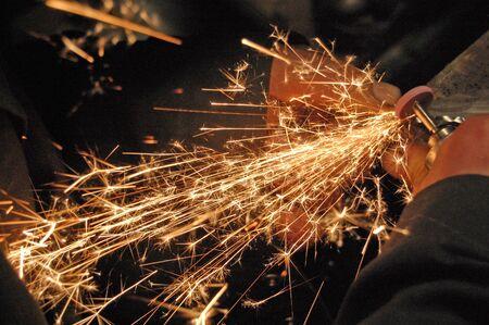Blacksmith grinding detail at his workshop.  Image full of sparkles