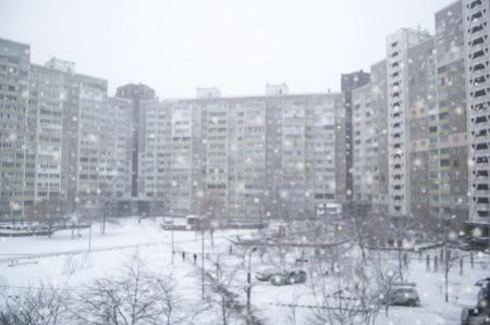 Appartment building in winter, snowfall. December. Defocused precinct in snow. Trees in front side.