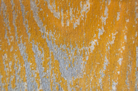 Old yellow cracked paint pattern on a wooden background. Peeling paint.