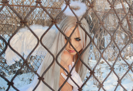 Angel is sitting behind bars Stock Photo