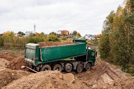 Un gran camión volquete verde de 70 toneladas trajo arena a un nuevo sitio de construcción para agregar tierra