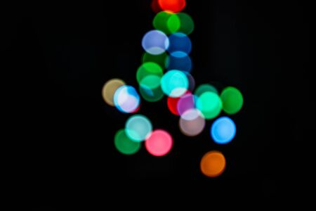 multicolored blurry bokeh lights on a black background in the silhouette of a Christmas tree
