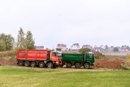 Two large green and red 70-ton dump trucks brought sand to the site to add to the new construction site