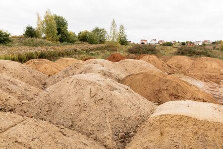 En una parcela de tierra asignada para la construcción de una casa hay muchos montones de arena, buen tiempo. Foto de archivo