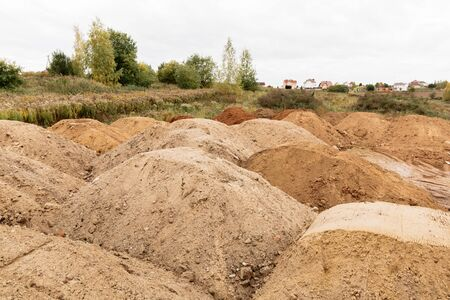 On a plot of land allotted for the construction of house lies a lot of piles of sand, good weather.
