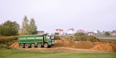 A large green 70-ton dump truck brought sand to a new construction site to add land