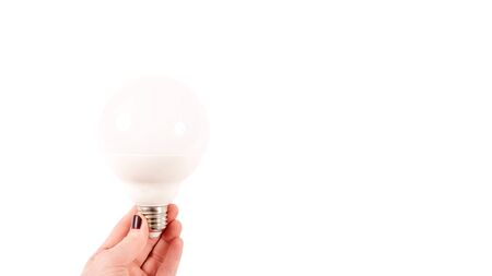 Female hand holding a big matte light bulb on white background, close-up