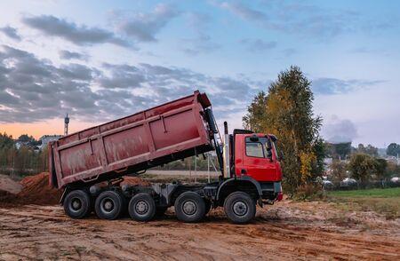 A dump truck is dumping gravel on an excavation site, building landscape