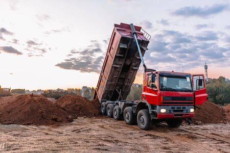 Un camión volquete está descargando grava en un sitio de excavación, paisaje de construcción Foto de archivo
