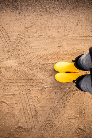 Feet in yellow rubber boots stand on a wet sandy country road Stock Photo