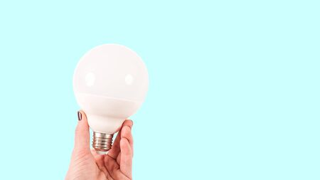 Female hand holding a big white matte light bulb on blue background, close-up