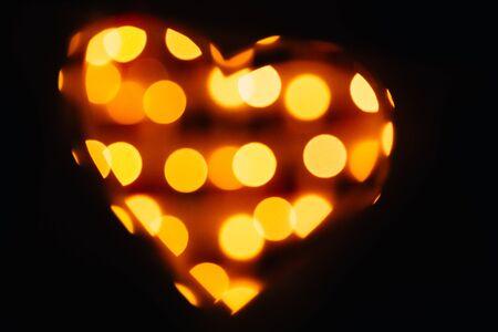 silhouette of the symbol of love - hearts against the bright orange blurred lights, valentine card Archivio Fotografico - 137348378
