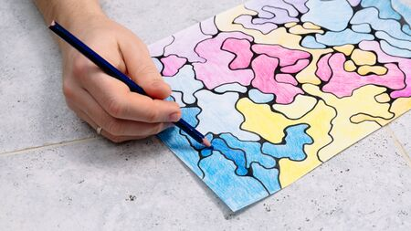 man draws an abstract imaginary picture with a pencil and decorates it with different colors, a psychological test for the subconscious