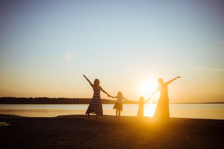 Silhouette of people holding hands with each other on sunset light background. Good mood and pastime among the younger and older generation. Friendship and freedom. Beautiful landscape.