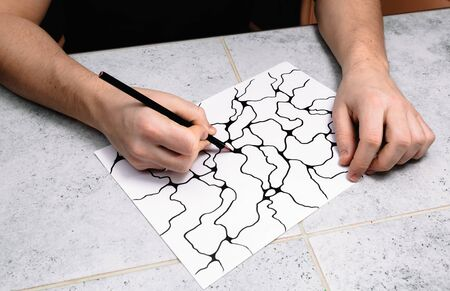 Man is drawing an abstract imaginary picture of curves by a black pencil in his hand. A psychological art therapy tests. Identification of the unconscious, subconscious, the depths of the human brain. Psychological expressionism.