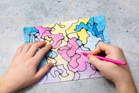 man draws an abstract imaginary picture with a pink pencil and decorates it with different colors, a psychological test for the subconscious