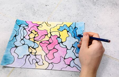 man draws an abstract imaginary picture with a pencil and decorates it with different colors, a psychological test for the subconscious Foto de archivo