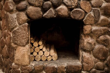 natural stone fireplace with hearth and logs Stock Photo