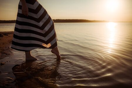 During sunset a girl in a striped dress walks along the beach, only her barefeet in the water are visible. Circles of life diverge on water. The state of calm and pacification. Close-up