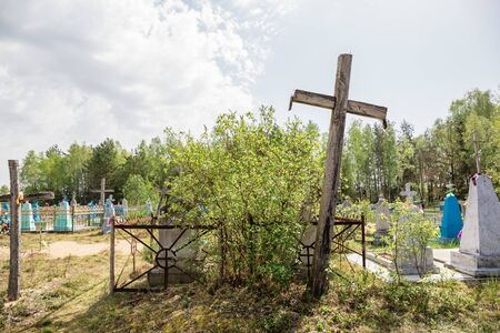An old cemetery with tombstones and large wooden crosses. Christian burials. Western Belarus.