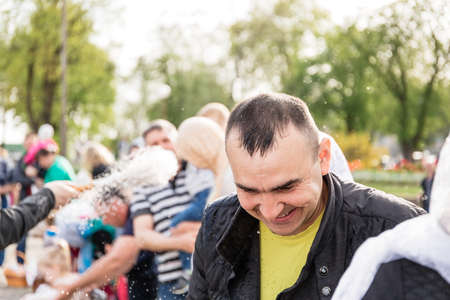 Beryoza, Belarus - April 27, 2019: The priest follows the Christian religious tradition of sprinkling believers and their Easter cakes, painted eggs and candles, with holy water, near the church. Editorial