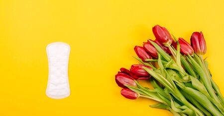 Top view of women's sanitary pads, panty liners on a yellow background. Flat lay with a bouquet of flowers.