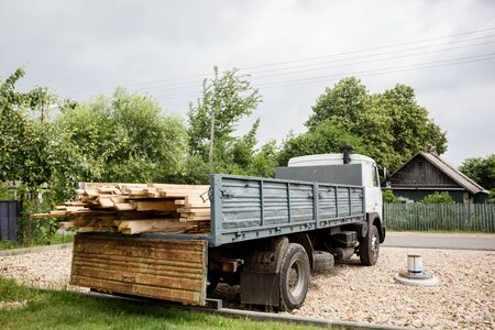 A planed board lies on board the truck. Building materials were brought to the construction site. Chopped wood for interior use. Cargo transportation of oversized items. Stok Fotoğraf