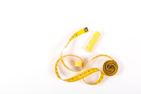 A centimeter tape and two spools of yellow thread on a white background in a minimalistic style with a place for text. Items for needlework, embroidery, sewing and cutting clothes. Studio shot, side view.