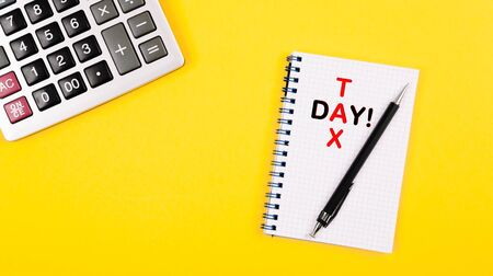 Tax day written in red and black color as a rebus into the notepad. Accountant desktop layout with calculator and important day reminder. Positive yellow background as a symbol of honest taxes. Stock Photo