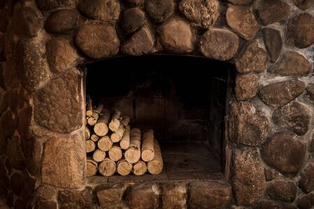 natural stone fireplace with hearth and logs