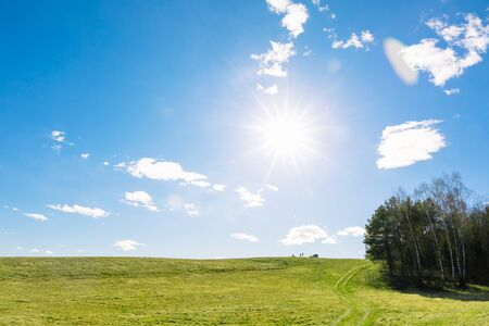 Green field and blue sky with sun and clouds. People by car came to rest in a beautiful place. Summer trip with the whole family. Can be used as a picture for interior decoration. Untouched nature.