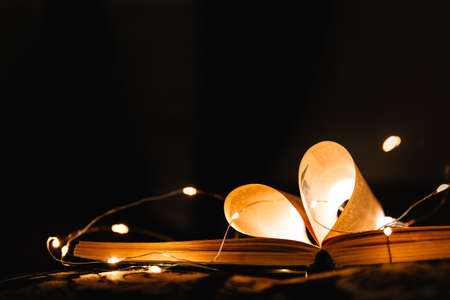 art book novel with sheets in the shape of a heart decorated with bright garland lights and highlights in the background, a romantic symbol of love, macro-shot
