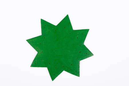 Step by step instruction how to make new year or Christmas tree. Cardboard is carved in the shape of a star, imitating a tier of branches and painted in green. Holes for toys are made around the edges