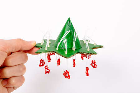 Step by step instruction how to make Christmas tree. Make a cone imitating the top from paper and glue it to a small star. Fasten the thread with a drop of glue and cut the excess. Hand holds craft.