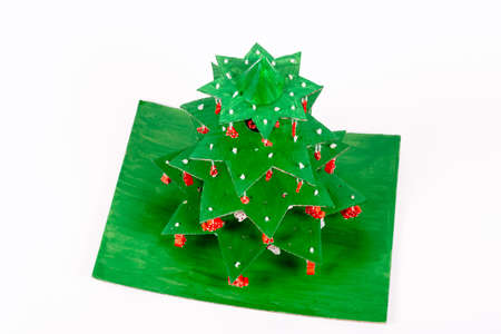 Step by step instruction how to make Christmas tree. Using glue we connect the star tiers decorated with pasta to each other with pieces of tube from paper towels and glue on a cardboard stand. Top wiew.